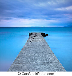 Broken concrete pier or jetty and rocks on a blue sea. Hills on background