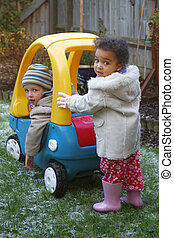 A young mixed race girl pushing a boy in a big toy car