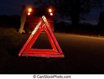 car driver awaits recovery after experiencing a vehicle breakdown at night with warning triangle