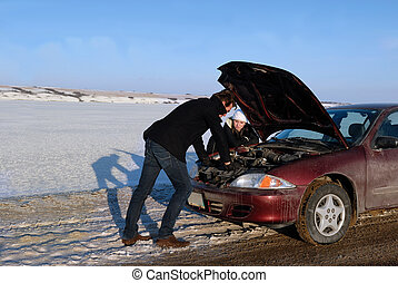 A stranded couple with broken down car on side of the road in winter
