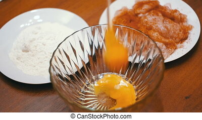 Broken Egg Falls into a Transparent Bowl on Background of Flour and Meat in the Home Kitchen. Slow Motion