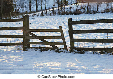 broken fence in the snow at sunset