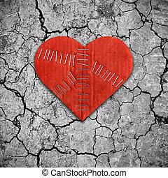 Broken heart on dry cracked soil