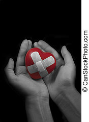 Broken heart  - Photo of hands holding a wounded heart.