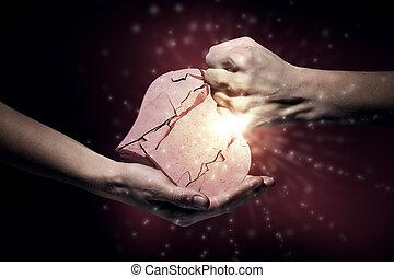 Broken  heart - Close up of human hand breaking stone heart