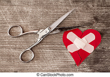 Broken heart with bandage and scissors