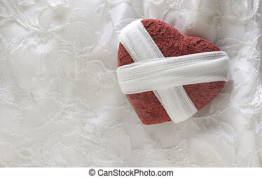 Broken heart concept of a red lace heart wrapped with gauze against a white lace background.