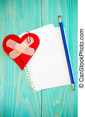 Broken heart with sheet of paper