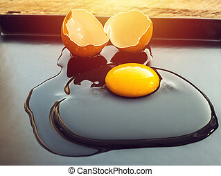 broken hen egg on black dish with morning light