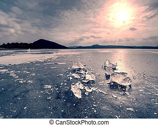 Broken ice pieces on frozen sea with pink and blue shadows