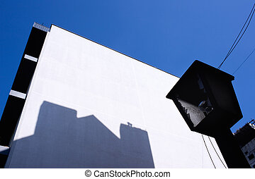 Broken lantern on a white wall with shadow