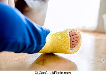 Broken leg in cast of unrecognizable little boy.