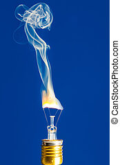 Broken light bulb burn out with flame on blue