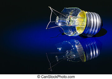 Broken light bulb on shiny blue surface artistic conversion