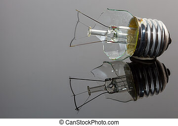 Broken light bulb on shiny silver surface