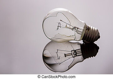 Broken light bulb on shiny surface