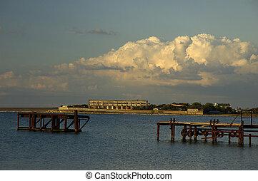 Broken metal bridge in the open sea with blue sky