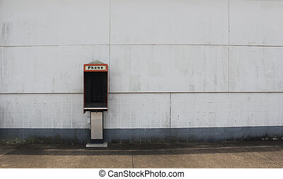 Broken Phone Booth on Empty Wall of Abandoned Building