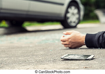 Broken phone next to a hand of a victim lying on the street
