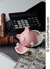 Broken piggy bank, cash and wooden gavel on keyboard. Auction and bankruptcy concept. Vertical image