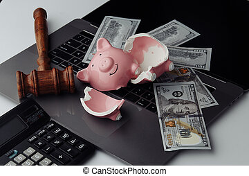 Broken piggy bank, cash and wooden gavel on laptop. Business and bankruptcy concept