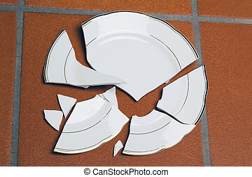 A broken plate lying on a floor. Symbolic photo for divorce and separation.