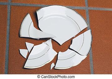 Broken plates - A broken plate lying on a floor. Symbolic...