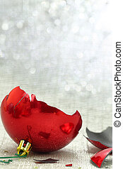 Broken red Christmas ornament with silver bokeh background