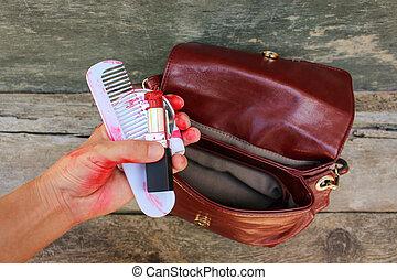 Broken red lipstick, mirror, comb in women hand.
