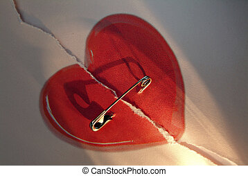 broken red love heart repaired with a safety-pin