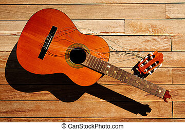 Broken spanish guitar neck on wooden deck