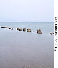 broken stone bridge on sea