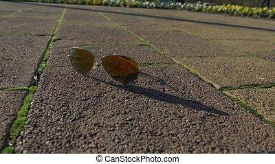 broken sunglasses on the floor. someone drops sunglasses on...