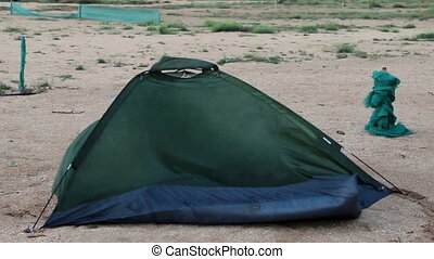 broken tent at the beach - green broken camping tent on the...