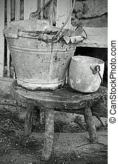 tin bucket and an aluminum pot over the stool of the old stable