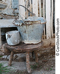 old broken tin bucket and an pot over the stool of the old abandoned stable