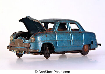 Broken Tin Toy Car - A battered and broken tin toy car, with...