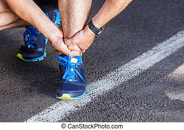 Broken twisted ankle - running sport injury. Male runner...