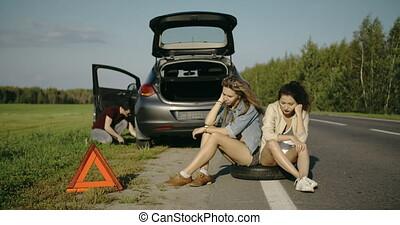 Broken wheel man changing tire help two female friends...