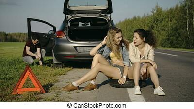 Broken wheel man changing tire help two friends - Broken...