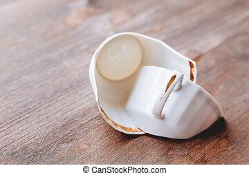 Broken white cup on wooden background. Damaged mug with golden decoration.