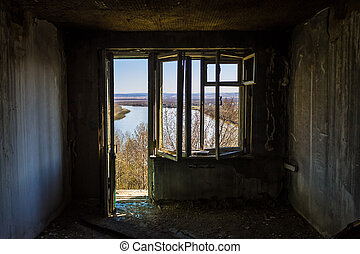 Broken window overlooking the river in an old, abandoned and burnt building