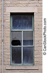 broken window pane in an old abandoned house with stone walls and green frame