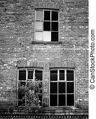 broken windows in a derelict abandoned brick building