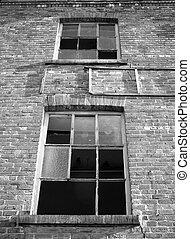 broken windows in an abandoned industrial building