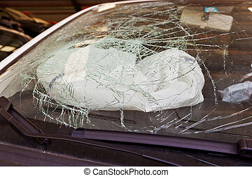 broken windshield and airbag - a broken windshield in an...