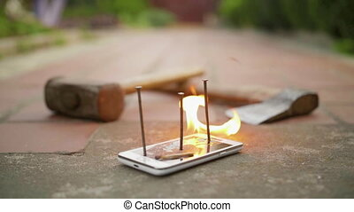 Broken with nails mobile phone on ground is on fire in slow motion