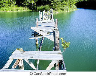Broken wooden bridge after disaster over quiet lake...