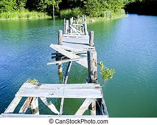 Broken wooden bridge after disaster over quiet lake...