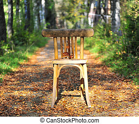 Broken wooden chair on the road in forest